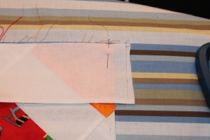 After Steam-easing: Border strip extends past the raw edge of the quilt top and the quilt lays flat.