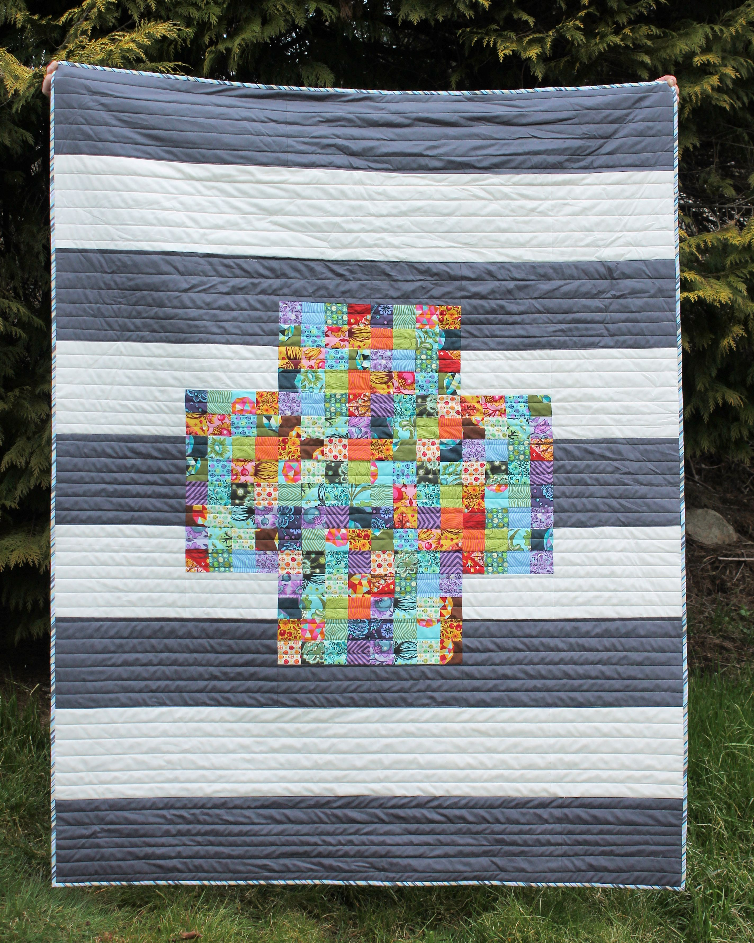 I quilted in straight lines and used my two favorite Freespirit solids –  Mist and Manatee – for the background stripes. This quilt lives on my couch  and ... e808e34609985